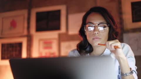 vídeos y material grabado en eventos de stock de atractiva mujer trabajando en la computadora portátil tarde en la noche - en búsqueda