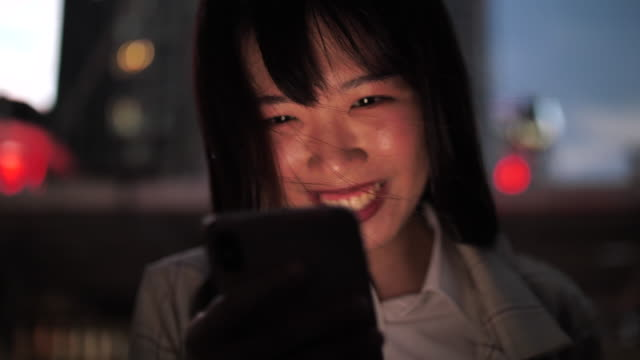 vídeos de stock e filmes b-roll de attractive young asia woman using mobile phone after work - leste