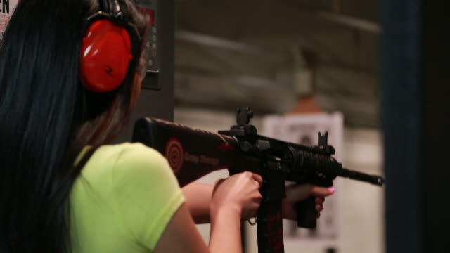 attractive young asian woman fires an ar-15 assault rifle at an indoor gun range - target shooting stock videos and b-roll footage