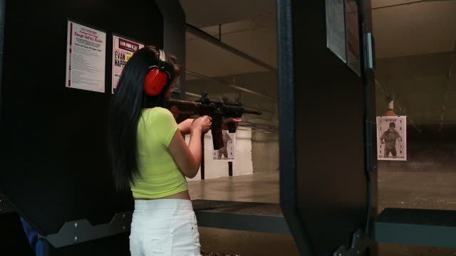 attractive young asian woman fires an ar-15 assault rifle at an indoor gun range. - ライフル点の映像素材/bロール
