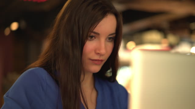Attractive young brunette woman using a laptop, 5.