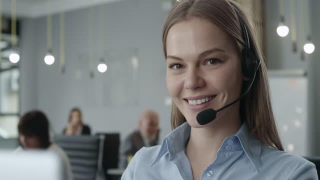 attraktive junge call center-agenten - headset stock-videos und b-roll-filmmaterial
