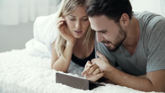 vídeos de stock e filmes b-roll de attractive young couple watching tablet at home - casal casado