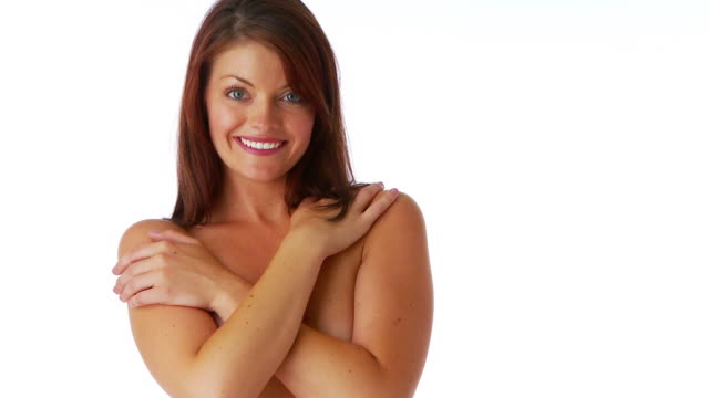 Attractive young female covering breasts with arms