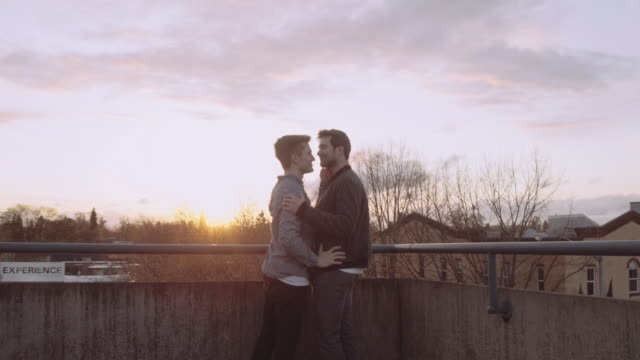 Attractive young male couple holding each other on top of a parking structure