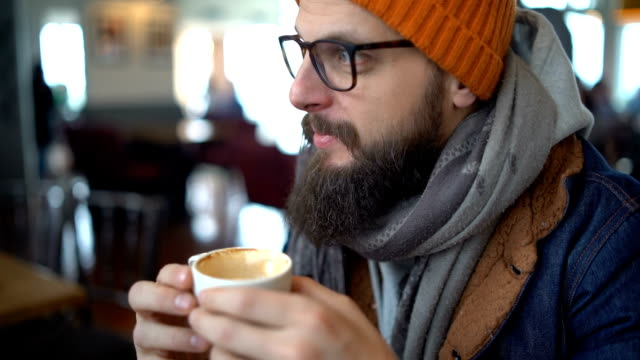attractive young man drinking coffee at cafe - negative emotion stock videos & royalty-free footage