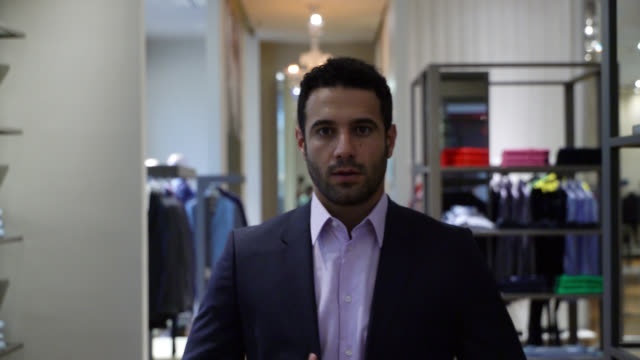 attractive young man looking at himself at the mirror while trying on a suit - jacket stock videos & royalty-free footage