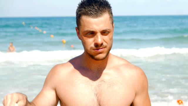 stockvideo's en b-roll-footage met aantrekkelijke jonge man op het strand direct kijken camera - badmeester