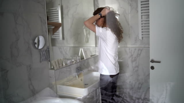 attractive young man tying up his hair in bathroom - handsome people stock videos & royalty-free footage