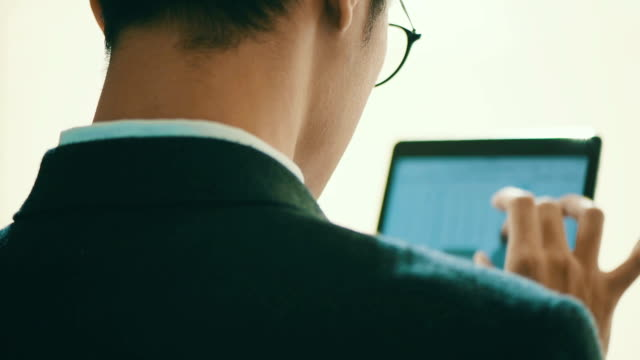 魅力的な若い男を使用してデジタル タブレット コンピューターのタッチ スクリーン、計算されました。 - マルチメディア点の映像素材/bロール