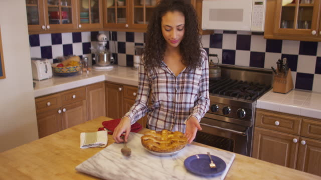 Attractive young mixed ethnic woman cutting apple pie