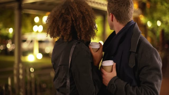 attractive young multi ethnic couple drinking coffee on a date at night.  stylish millennial black and white man and woman holding drinks talking with each other on city street. 4k - coffee variation stock videos & royalty-free footage