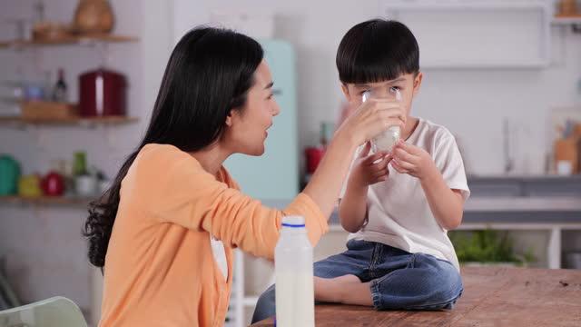 vídeos de stock, filmes e b-roll de mãe jovem e sorridente atraente derramando leite em copos para seu filho tomar café da manhã em casa. - beber