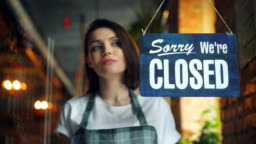 Attractive young waitress changing closed to open sign on cafe door smiling