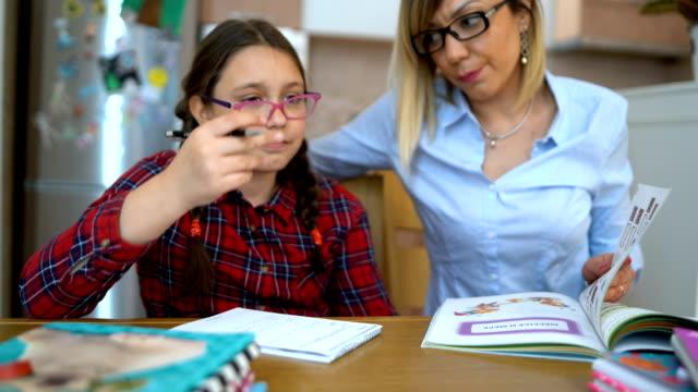 attraktiv ung kvinna och hennes lilla söta dotter sitter vid bordet och gör läxor tillsammans. mamma hjälper dotter med sina skol klasser. - lärarinna bildbanksvideor och videomaterial från bakom kulisserna