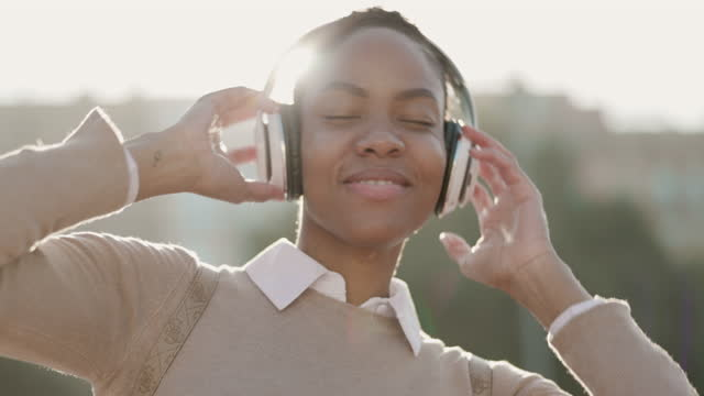 attractive young woman dancing while listening to music outdoors in the city - short hair stock videos & royalty-free footage