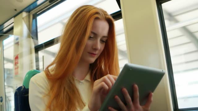 Aantrekkelijke jonge vrouw op een trein met behulp van haar digitale tablet.