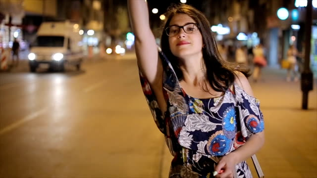 attractive young woman raising her arm to call a taxi in a busy city at night - stop sign stock videos and b-roll footage