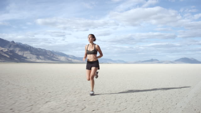 slo mo: attractive young woman running in the desert - running shorts stock videos & royalty-free footage