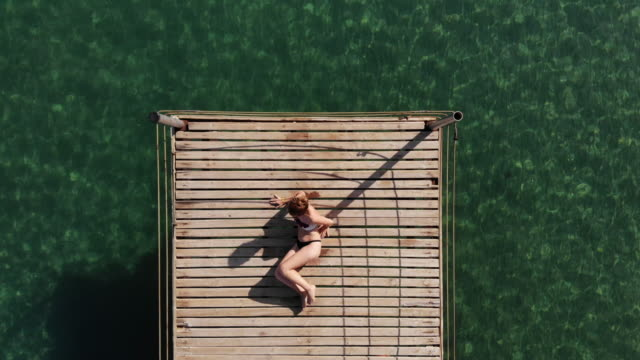stockvideo's en b-roll-footage met aantrekkelijke jonge vrouw zonnebaden in de buurt van de zee. - pier