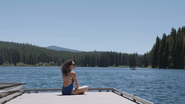 stockvideo's en b-roll-footage met aantrekkelijke jonge vrouw zonnebaden naast een meertje - fatcamera