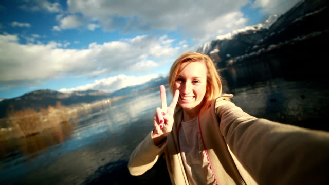 Attractive young woman taking selfie by the lake