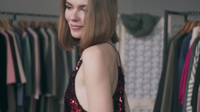 attractive young woman trying on red sequin dress - sequin stock videos & royalty-free footage