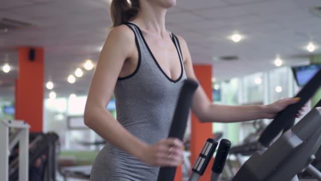 vídeos de stock, filmes e b-roll de mulher jovem e atraente usando um treinador cruzada no ginásio - aparelho de musculação