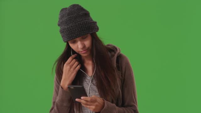 stockvideo's en b-roll-footage met attractive young woman wearing earbuds to listen to music on greenscreen - in ear koptelefoon