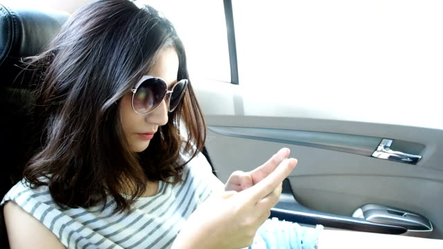 Attractive young woman with sunglasses using mobile phone