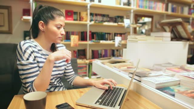Attraktive junge Frau Arbeiten an Ihrem laptop.