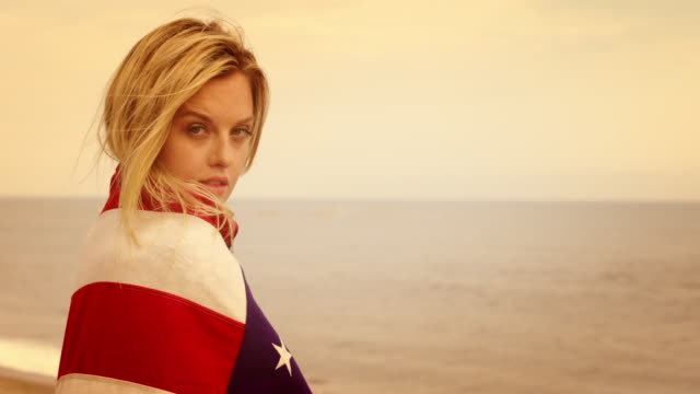 attractive young woman wrapped in stars and stripes at the beach 4k - vesper stock stock videos & royalty-free footage