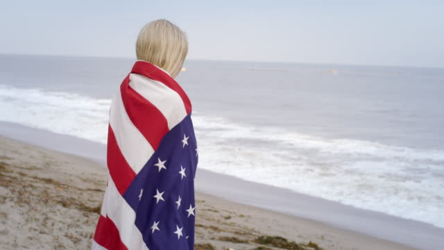 attractive young woman wraps herself in stars and stripes at the beach 4k - vesper stock stock videos & royalty-free footage