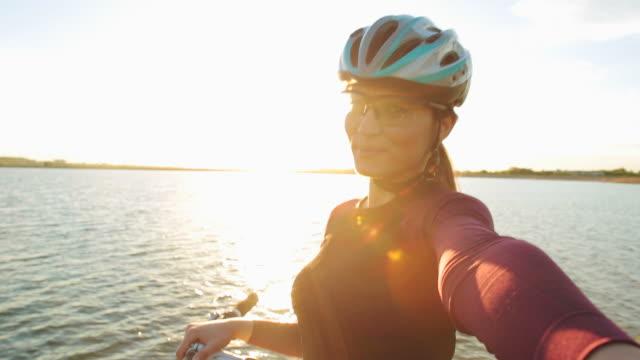 stockvideo's en b-roll-footage met aantrekkelijke jonge vrouwen wielrenner nemen van selfies bij zonsondergang. - zelfportret fotograferen