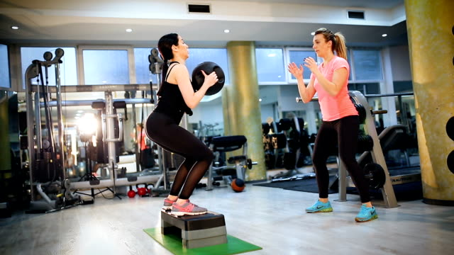 Attractive young women exercising pilates with weight ball