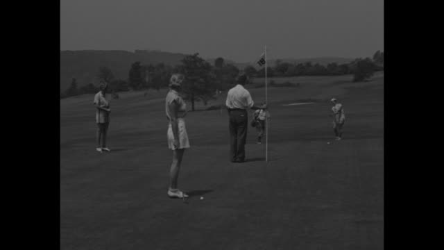vs attractive young women in shorts tee off follow ball on green / vs golf star beatrice gottlieb wearing shorts putts sinks shot / sot gottlieb... - shock tactics stock videos and b-roll footage