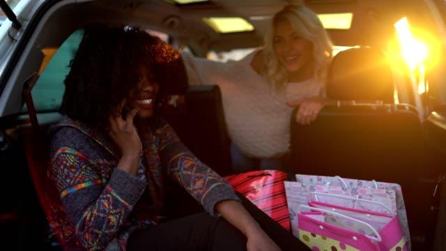 魅力的な若い女性は、成功したショッピングの日の後に車の中でリラックスして夕日を楽しんで - 喜び点の映像素材/bロール