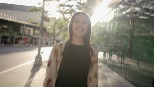 attractive young women walking in the city streets at sunset light. urban lifestyle portrait of caucasian female model - 歩道点の映像素材/bロール