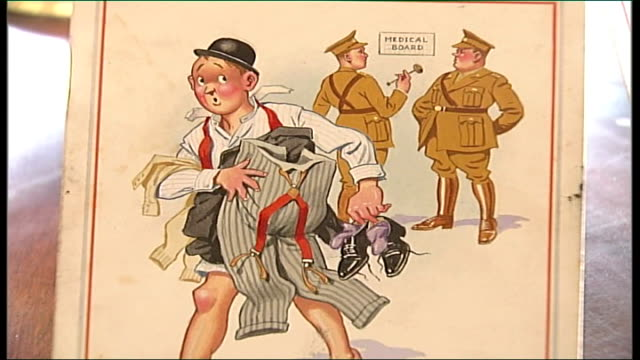 auction of saucy postcards close shot postcard of half undressed businessman with two army officers behind as voiceover caption read sot - fetishism stock videos & royalty-free footage