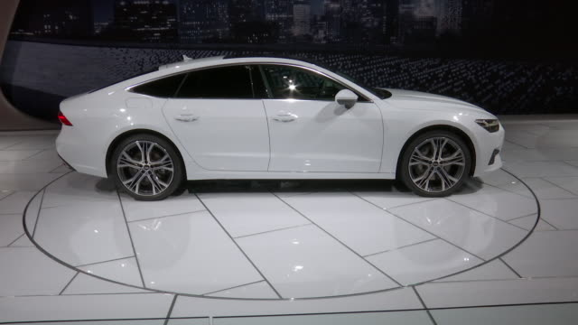 WS Audi A7 revolving on turntable / CU front end / TILT DOWN from ceiling WS front end / ZO WS front wheel / CU rear end / TILT DOWN from ceiling WS...