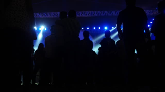 Audience applauding and clapping for a performance accompanied with an elaborate sound and light display