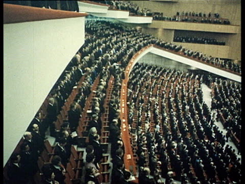 Audience applauding and singing anthem former USSR flag printing press of Pravda newspaper crowd cheering Brezhnev and other dignitaries walking on...