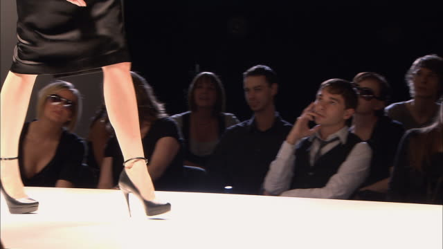 ms pan audience at fashion show watching model on catwalk/ london, england - runway stock videos and b-roll footage