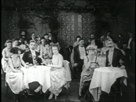 vidéos et rushes de b/w 1919 audience at tables in club jumping slightly in chairs in unison / short - 1910 1919