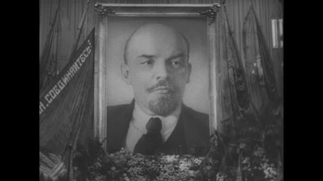 Audience at the Bolshoi Theatre / portrait of Vladimir Lenin / Nikita Khrushchev and others standing at dais applauding / audience at Bolshoi sitting...