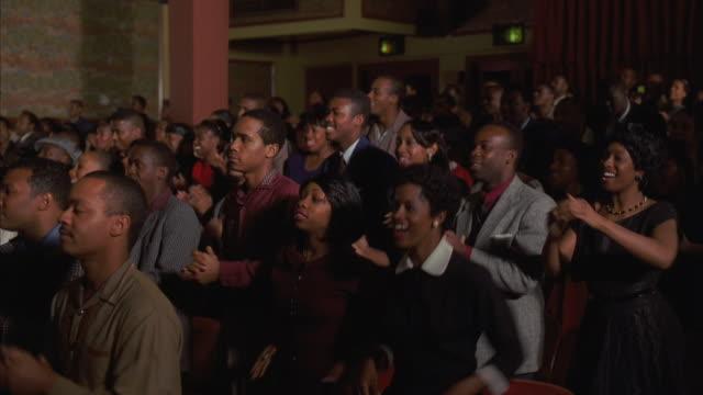 stockvideo's en b-roll-footage met ws pan audience clapping and singing - gospelmuziek
