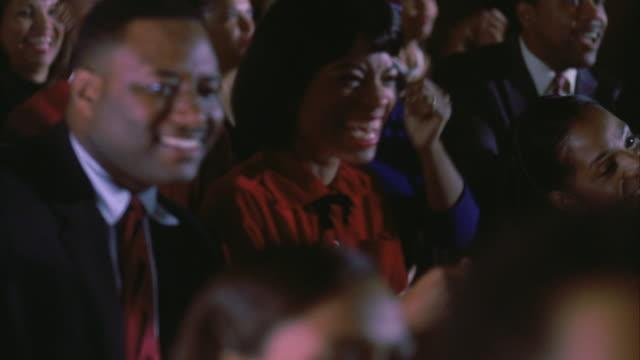 stockvideo's en b-roll-footage met cu pan selective focus audience clapping and singing - gospelmuziek