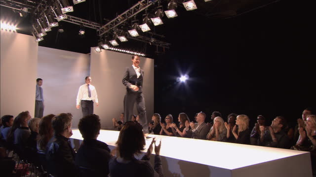 MS Audience clapping at fashion show/ TU MS Three male and one female model, all wearing business wear, walking and posing on catwalk/ London, England