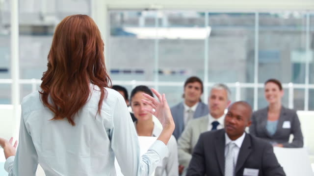 Audience clapping for a businesswoman