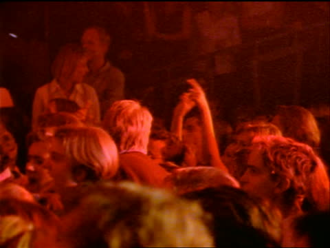 Audience dancing in crowded club during rock concert